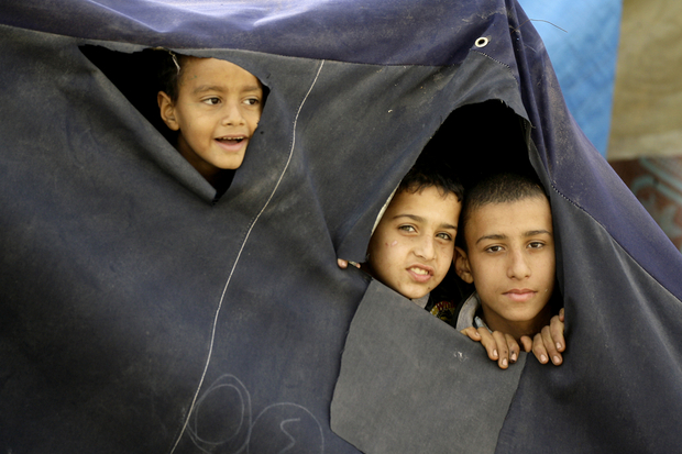 Young Palestinian refugees, who fled the Yarmuk refugee camp in Syria where they were previously residing due to the ongoing conflict, peer through holes made in their tent as they prepare to move to new houses built by the United Nations Development Programme (UNDP) at the Palestinian refugee camp of Ain El-Helweh, near the southern Lebanese coastal city of Sidon, on January 31, 2014. The United Nations distributed food in the Syrian capital's besieged Yarmuk Palestinian refugee camp for a second day in a bid to help tens of thousands of trapped civilians. AFP PHOTO / MAHMOUD ZAYYAT / AFP PHOTO / MAHMOUD ZAYYAT